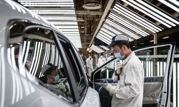 An employee wearing a face mask works on an assembly line at an auto plant of Dongfeng Honda in Wuhan city, Hubei Province, China, on April 7, 2020. (Photo by STR/AFP via Getty Images)