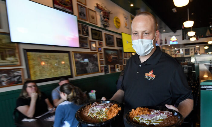 General manager Steven Hanson carries food to a table at Hussong's Cantina in Boca Park Fashion Village in Las Vegas on May 9, 2020. (Ethan Miller/Getty Images)