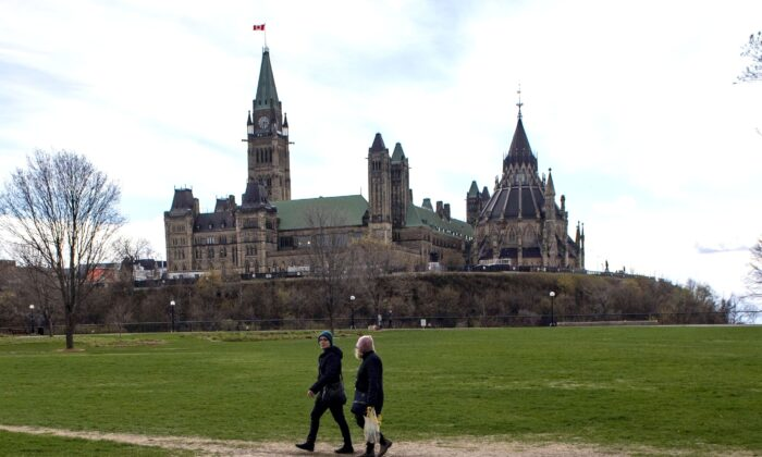 Parliament Hill is seen in the background as people walk through Major's Hill Park in Ottawa during the COVID-19 pandemic, on May 9, 2020. (The Canadian Press/Justin Tang)