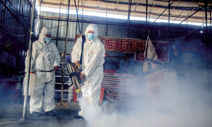 This photo taken on May 6, 2020 shows volunteers spraying disinfectant at a market as a preventive measure against the COVID-19 coronavirus as it prepares to reopen in the border city of Suifenhe in China's northeastern Heilongjiang province. (STR/AFP via Getty Images)