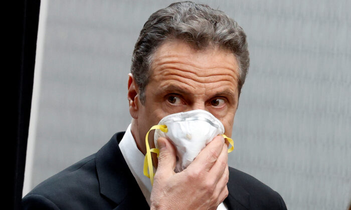New York Governor Andrew Cuomo holds a protective mask to his face as he arrives for a daily briefing at New York Medical College in Valhalla, N.Y., on May 7, 2020. (Mike Segar/Reuters)