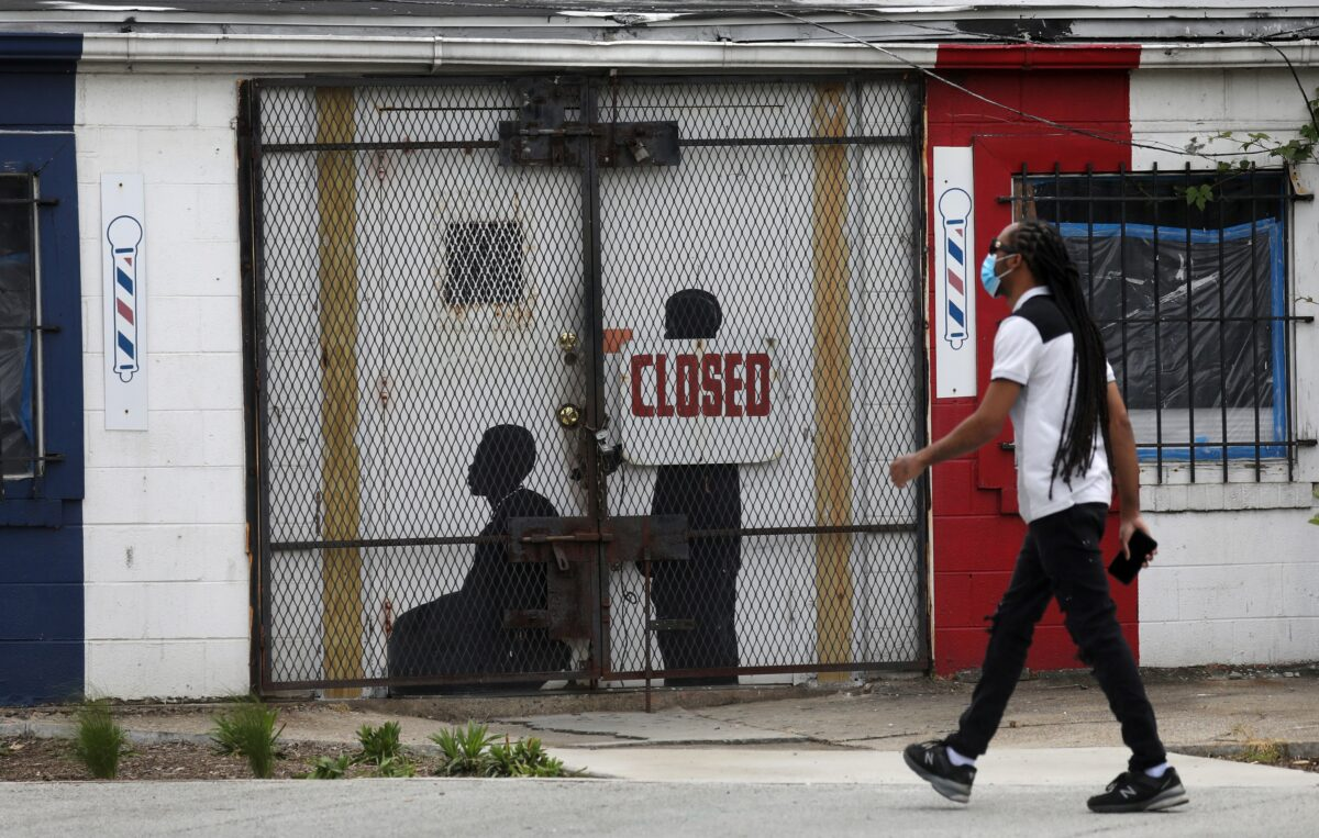 A pedestrian walks past a closed barber shop