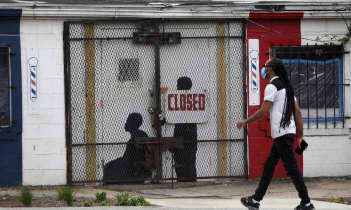 A pedestrian walks past a closed barber shop in Ward 7 as the CCP virus lockdown continues in Washington on May 8, 2020. (Leah Millis/Reuters)
