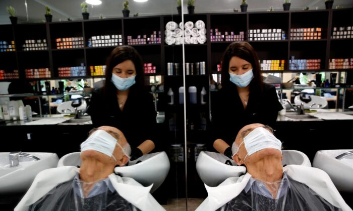 A man gets a hair cut at a hairdressing salon in Sevres, outside Paris, France, on May 11, 2020. (Christophe Ena/AP Photo)