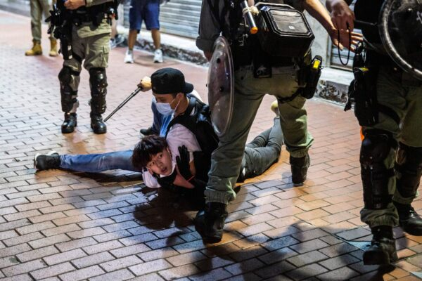 A pro-democracy demonstrator (C) is held on the ground before getting arrested by undercover police during a protest calling for the city's independence in Mong Kok district of Hong Kong on May 10, 2020. (Isaac Lawrence/AFP via Getty Images)