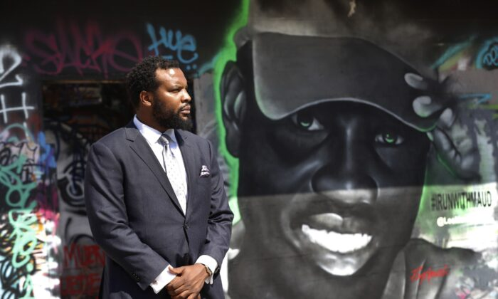 Lee Merritt, a lawyer representing the family of Ahmaud Arbery, poses for a photo by a mural in the likeness of Arbery painted by artist Theo Ponchaveli in Dallas on May 9, 2020. (Tony Gutierrez/AP Photo)