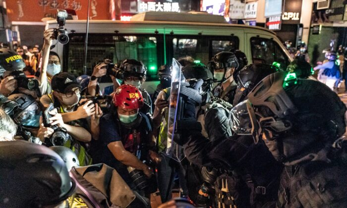 Riot police hold back members of the media during a demonstration in Mongkok district in Hong Kong, on May 10, 2020. (Anthony Kwan/Getty Images)