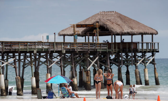 People enjoy a calm sunny day near the Cocoa Beach Pier in Cocoa Beach, Fla., on August 30, 2019.(Mark Wilson/Getty Images)