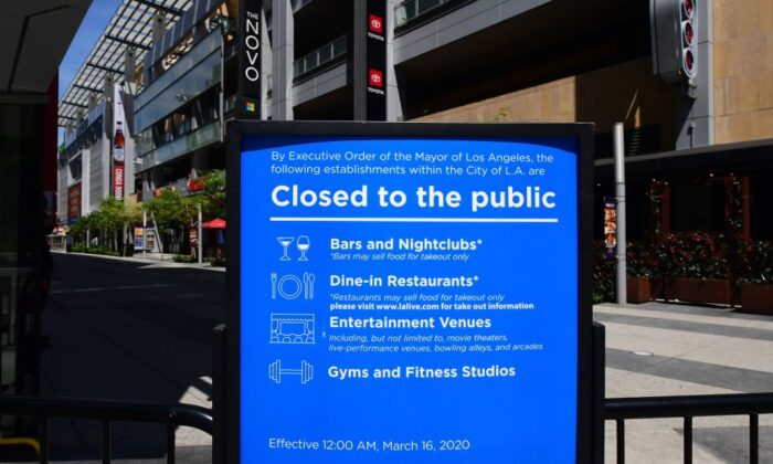 A sign in place since mid-March announces the temporary closures of restaurants, nightclubs, gyms, and entertainment venues at LA Live in Los Angeles on May 7, 2020. (Frederic J. Brown/AFP/Getty Images)