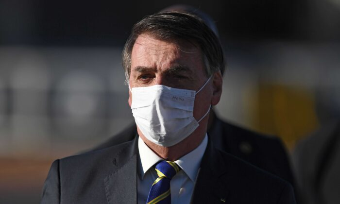 Brazilian President Jair Bolsonaro arrives at the flag-raising ceremony before a ministerial meeting at the Alvorada Palace in Brasilia, on May 12, 2020. (Evaristo Sa/AFP via Getty Images)