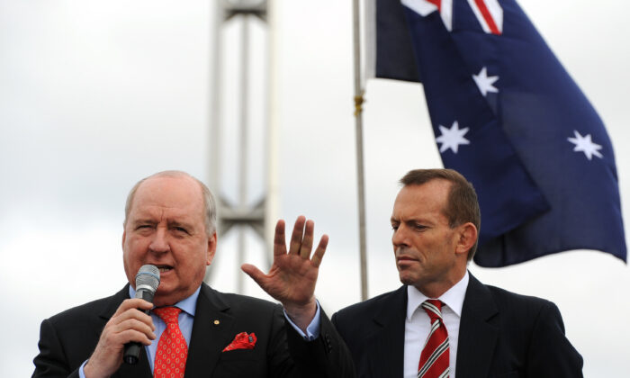 Conservative radio presenter Allan Jones (L) addresses the anti-carbon tax rally from The Convoy of No Confidence as Tony Abbott (R) looks on in front of Parliament House in Canberra on August 22, 2011.  (Torsten Blackwood/AFP via Getty Images)