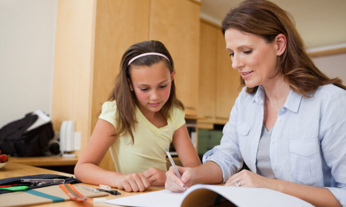 A mother helps her daughter with homework in a file photo. (Shutterstock)