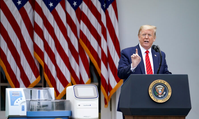 President Donald Trump stands next to CCP virus testing machines as he addresses a  press briefing in the Rose Garden at the White House in Washington, on May 11, 2020. (Kevin Lamarque/Reuters)