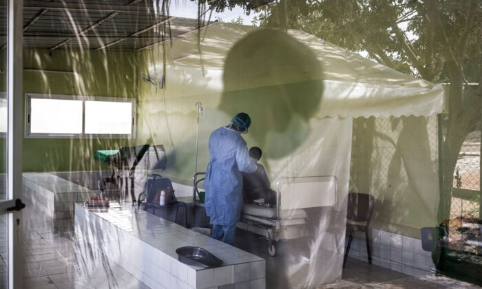 A Health worker tends to a patient inside a COVID-19 coronavirus ward that houses suspected cases in Pikine Hospital in Dakar on April 23, 2020. (John Wessels/AFP via Getty Images)