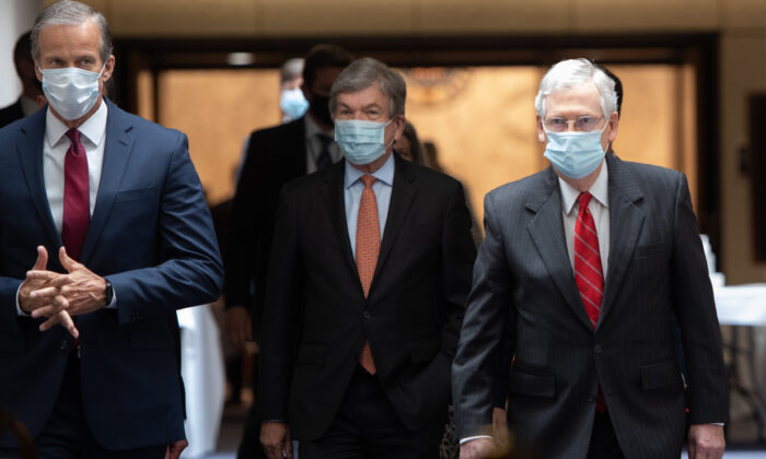 Senate Majority Leader Mitch McConnell (R-Ky.) (R), wearing a mask to protect himself and others from the CCP virus, arrives to speak to the media following the weekly Republican policy luncheon on Capitol Hill in Washington on May 5, 2020. (Saul Loeb/AFP via Getty Images)