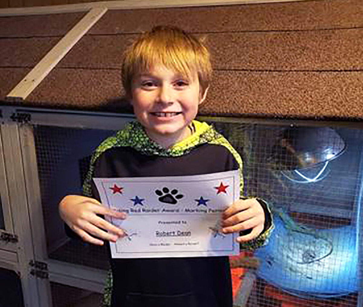 9-year-old Bobby Dean displays an award