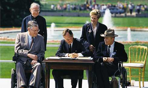 President George H.W. Bush signs the Americans with Disabilities Act into law on July 26, 1990. (Public Domain)