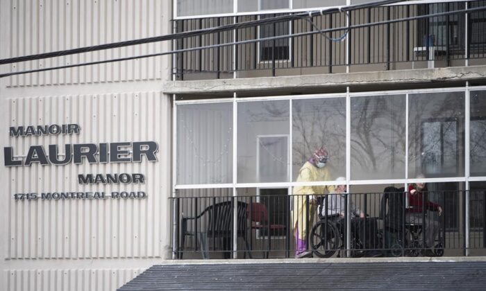 A health care worker wearing personal protective equipment (PPE) works with a resident on a balcony at the Laurier Manor in Ottawa, a long term care facility experiencing an outbreak of COVID-19, on April 26, 2020. (Justin Tang/The Canadian Press)