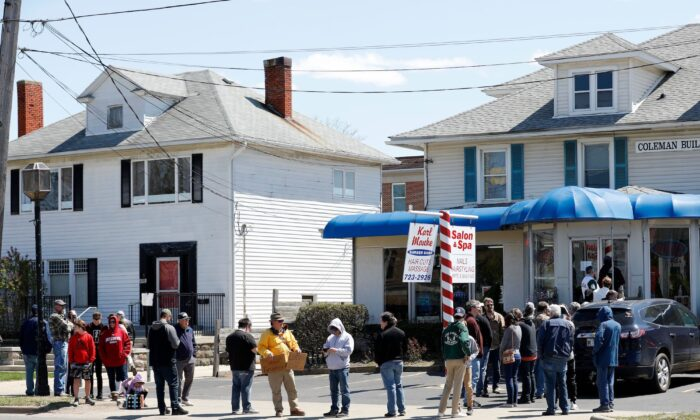 People wait in line to have their hair cut in front of the shop of Barber Karl Manke, who faces two misdemeanor charges for reopening his business despite state shutdown orders in Owosso, Mich., on May 12, 2020. (Jeff Kowalsky/AFP via Getty Images)