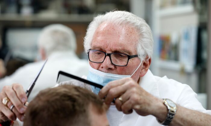Barber Karl Manke cuts a client's hair at his barber shop in Owosso, Mich., on May 12, 2020. (Jeff Kowalsky/AFP/Getty Images)