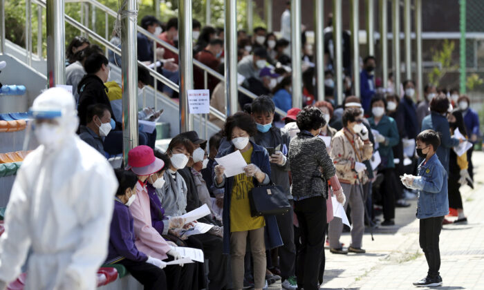 People wearing face masks wait to take a test for COVID-19 at a testing facility in Incheon, South Korea, on May 13, 2020. (Yun Tae-hyun/Yonhap via AP)