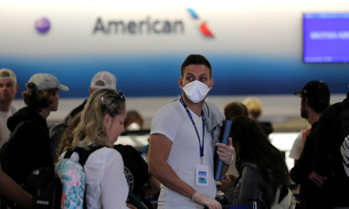 A passenger wearing a mask waits in line to check in for a flight as the Federal Aviation Administration (FAA) said it temporarily halted flights arriving at New York City airports and Philadelphia on Saturday after a trainee at the New York Air Route Traffic Control Center tested positive for coronavirus disease (COVID-19), at Miami International Airport, Miami, Fla., U.S., March 21, 2020. (Carlos Barria/Reuters)