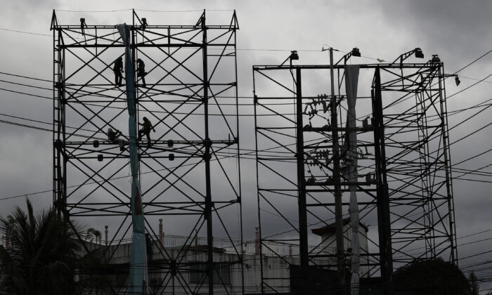 Dark clouds envelop the skies as workers fold a billboard to prepare for the coming of typhoon Vongfong in Manila, Philippines on  May, 14, 2020. (Aaron Favila/AP Photo)