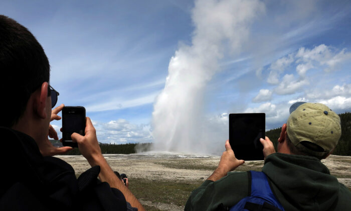People use phones and tablets to photograph Old Faithful geyser erupting in Yellowstone National Park in Wyo., on May 16, 2014. (Jim Urquhart/File Photo/Reuters)