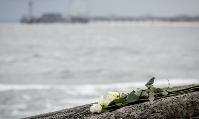 """Flowers are seen on the Northern Harbor Head in Scheveningen, where five surfers died after getting into difficulty in """"avalanche-like"""" sea foam caused by stormy conditions in the Netherlands on May 13, 2020. (Sem Van Der Wal/ANP/AFP via Getty Images)"""
