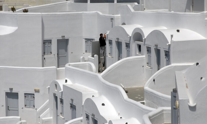 An employee makes repairs at a closed hotel in Fira,  Santorini, Greece, on May 7, 2020. (REUTERS/Alkis Konstantinidis)