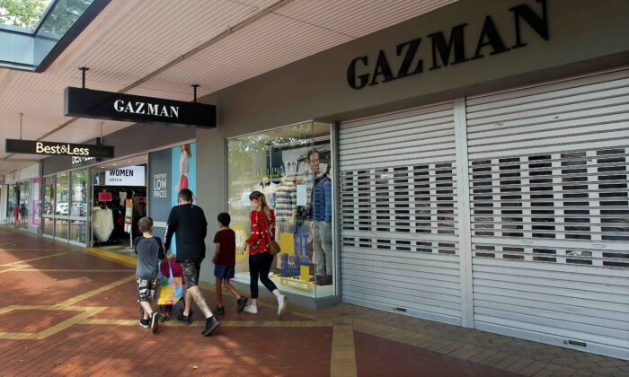 A family walks past closed retail stores along Peel Street in Tamworth, Australia, on April 4, 2020.(Lisa Maree Williams/Getty Images)
