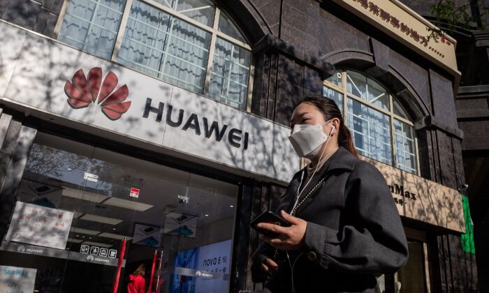 A woman wearing a face mask amid concerns over the COVID-19 coronavirus walks holding her smartphone past a Huawei shop (L) on a street in Beijing on April 22, 2020. (NICOLAS ASFOURI/AFP via Getty Images)