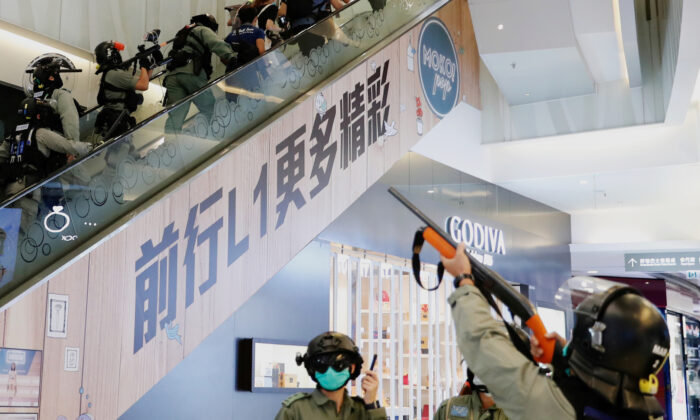 Riot police raise their pepper spray weapons inside a shopping mall as they disperse pro-democracy protesters during a rally, in Hong Kong, China, on May 10, 2020. (Tyrone Siu/Reuters)