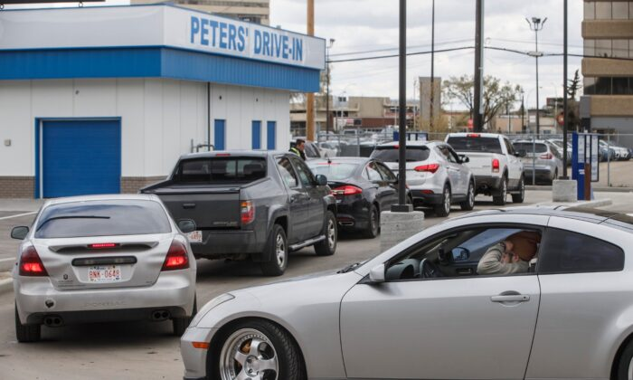 People line up to get food from Peters' Drive-In in Edmonton on May 11, 2020. (Jason Franson/The Canadian Press)