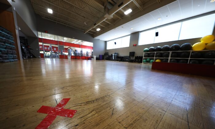 The letter X marked in red are placed on the floor of an exercise room more than seven feet apart at Gold's Gym Islip in N.Y. on May 13, 2020. (Al Bello/Getty Images)