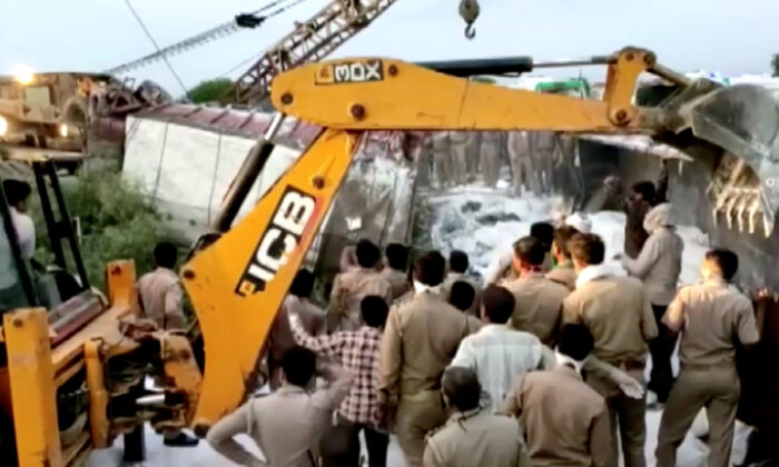 A police rescue team work to lift a truck at the site of an accident where a truck carrying migrant laborers collided with another, killing and injuring several people in Auraiya, Uttar Pradesh, India, May 16, 2020. (Ani/Reuters TV).