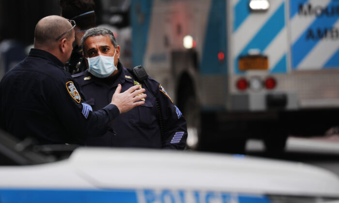 New York Police Department officers wear face masks as they attend to a crash involving a police officer in midtown along 5th Avenue in New York City on April 20, 2020. (Spencer Platt/Getty Images)