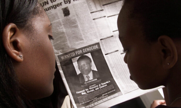 Readers look at a newspaper in Nairobi carrying the photograph of Rwandan Felicien Kabuga wanted by the United States on June 12, 2002. (George Mulala/Reuters)