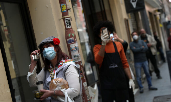 A woman wearing traditional attire of Madrid and a face mask listens to a woman singing from her balcony during the CCP virus lockdown in Madrid, Spain on May 15, 2020. (Susana Vera/Reuters)