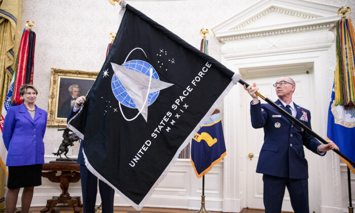 Gen. Jay Raymond (R), Chief of Space Operations, and CMSgt Roger Towberman (L), with Secretary of the Air Force Barbara Barrett present President Donald Trump with the official flag of the United States Space Force in the Oval Office of the White House in Washington, on May 15, 2020. (Samuel Corum-Pool/Getty Images)