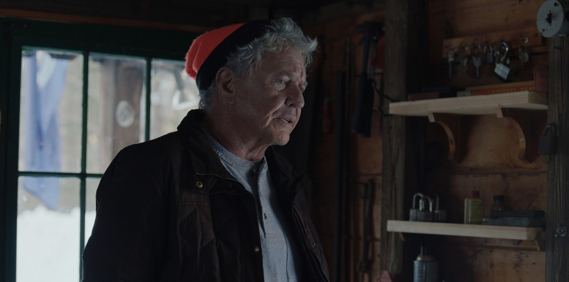 "Man in orange cap in cabin in ""Blood and Money"""