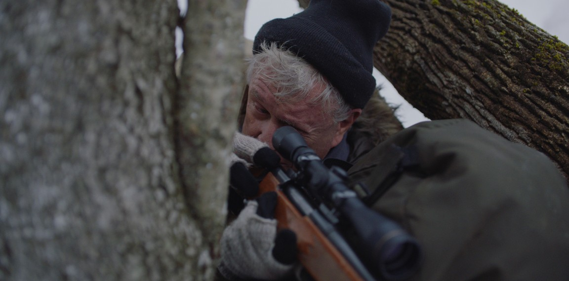 """man in tree with scoped rifle in """"Blood and Money"""""""