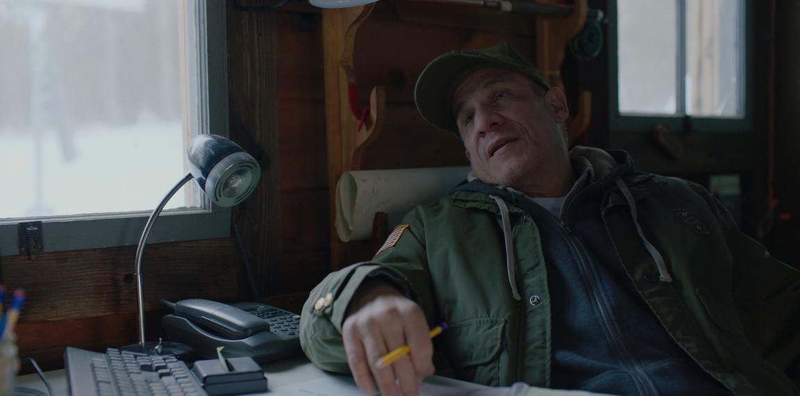 "park ranger at desk in ""Blood and Money"""