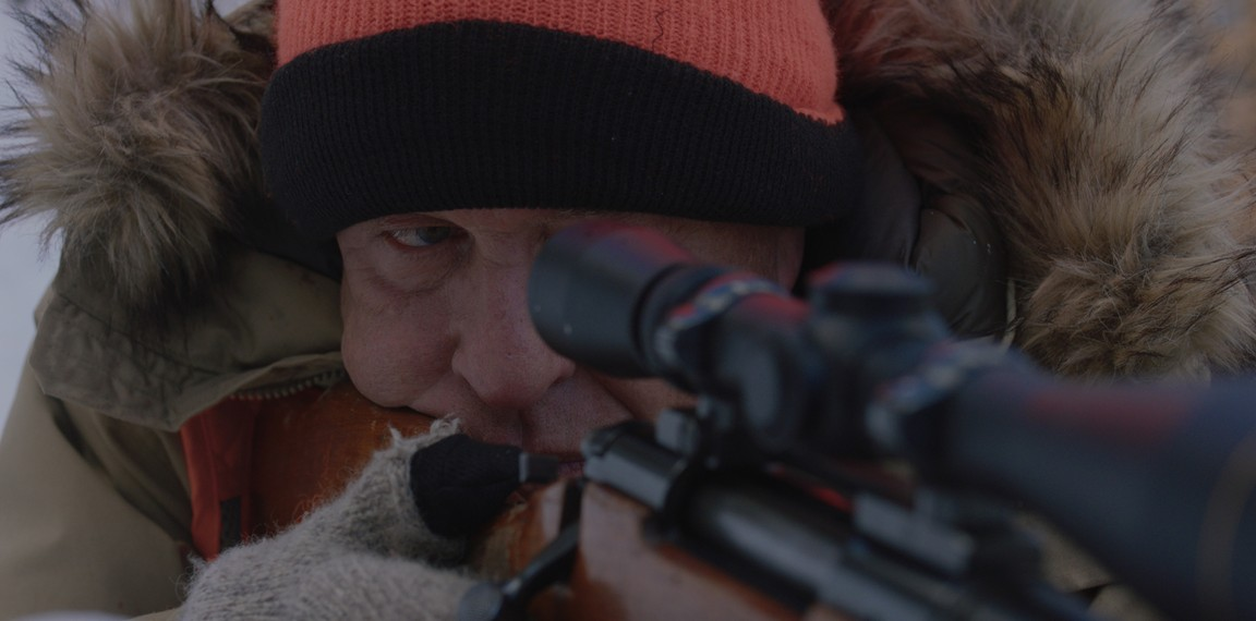 """man with orange cap and scoped rifle in """"Blood and Money"""""""