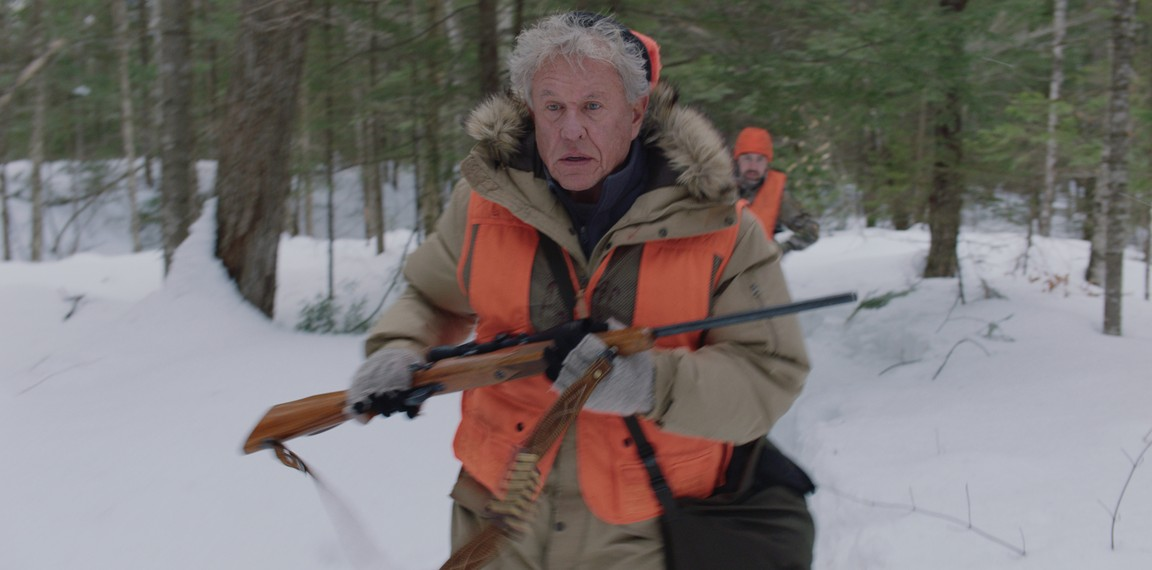 """man in orange hunting vest runs from another man in orange hunting vest in """"Blood and Money"""""""