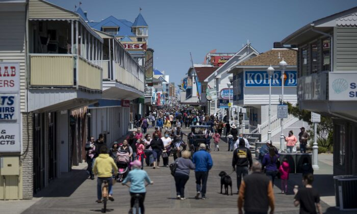 People walk on the boardwalk as the area re-opens from the coronavirus pandemic, in Ocean City, Maryland, on May 10, 2020. (Eric Thayer/Getty Images)