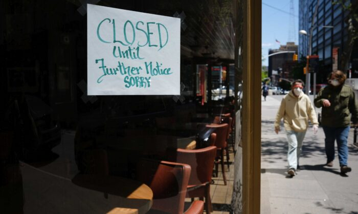 People walk through a shuttered business district in Brooklyn in New York City on May 12, 2020. (Spencer Platt/Getty Images)