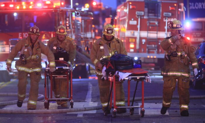 Los Angeles Fire Department firefighters push ambulance cots at the scene of a structure fire that injured multiple firefighters in Los Angeles, Calif., on May 16, 2020. (Damian Dovarganes/AP Photo)