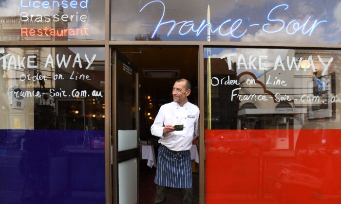 """Head chef Geraud Fabre of France-Soir waits for take-away orders in Melbourne on May 8 as Australia's government unveiled a three-stage plan to get the economy back to a """"new normal"""" by the end of July. (William West/AFP via Getty Images)"""
