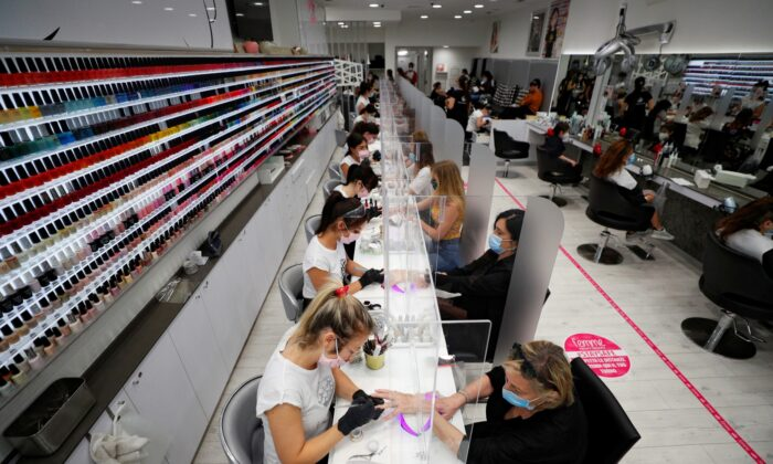 Women wearing protective masks work on the nails of customers at a beauty salon, as Italy eases some of the lockdown measures put in place during the CCP virus disease (COVID-19) outbreak, in Rome, Italy, on May 18, 2020. (Guglielmo Mangiapane/Reuters)